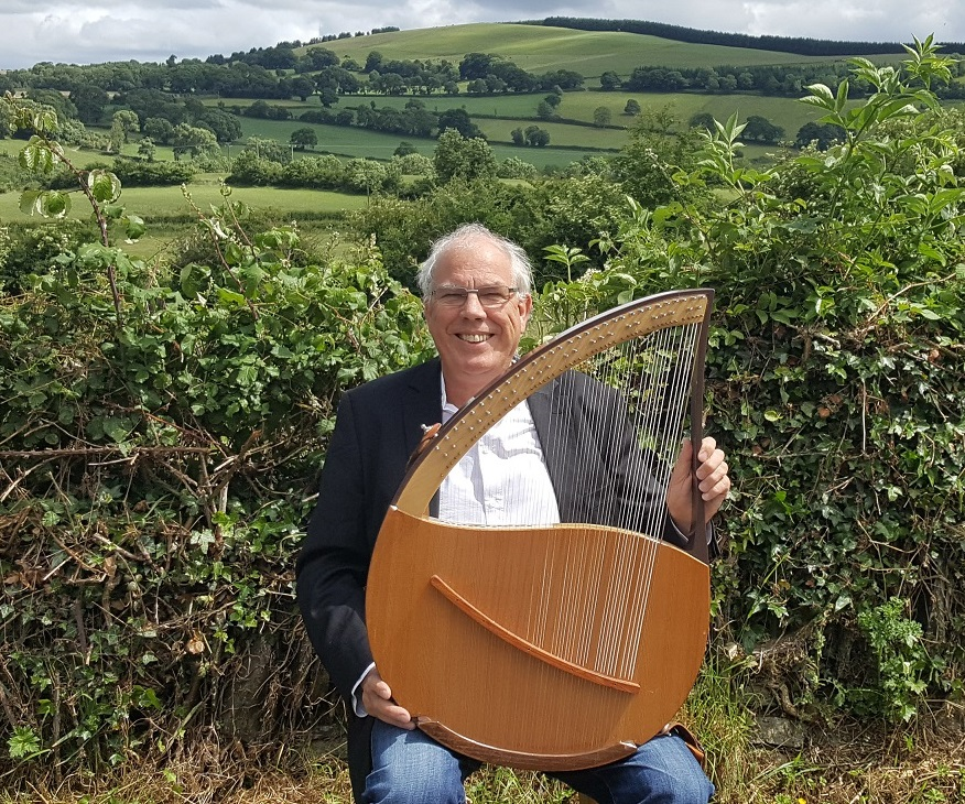 John in a landscape with his Wright-Lyre